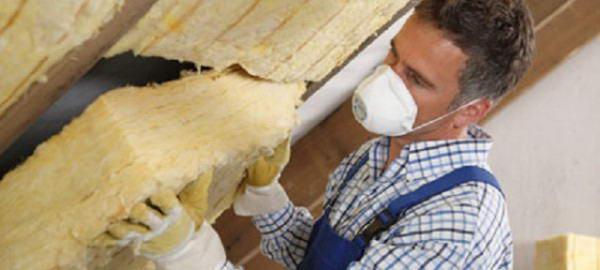 Процесс укладки минеральной ваты между стропилами крыши