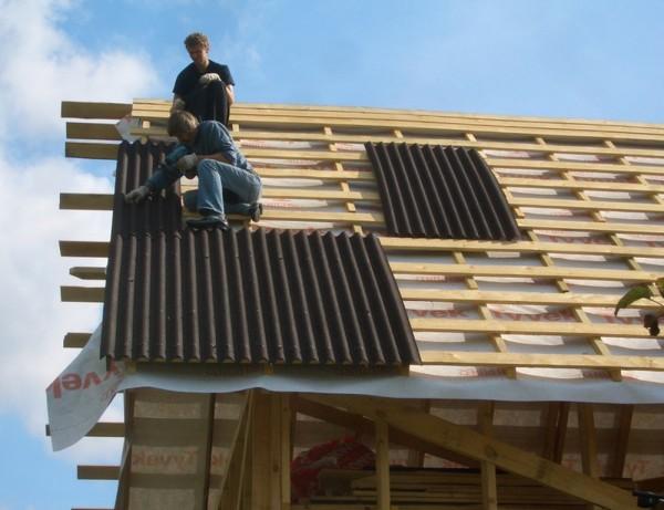 Процесс монтажа окрашенного шифера на обрешетку двухскатной крыши