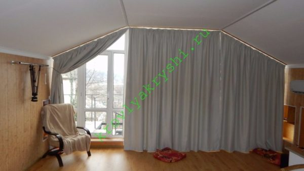 На фото хорошо видна форма подвесного потолка: под ригелем он горизонтальный, под стропилами — наклонный.